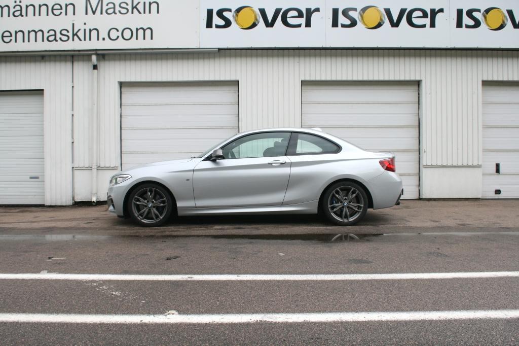 BMW M235i parkeret i pitten på ring Knutstorp. I profil er det coupeform der møder sedanform, men med kun to døre, ender den som coupe.
