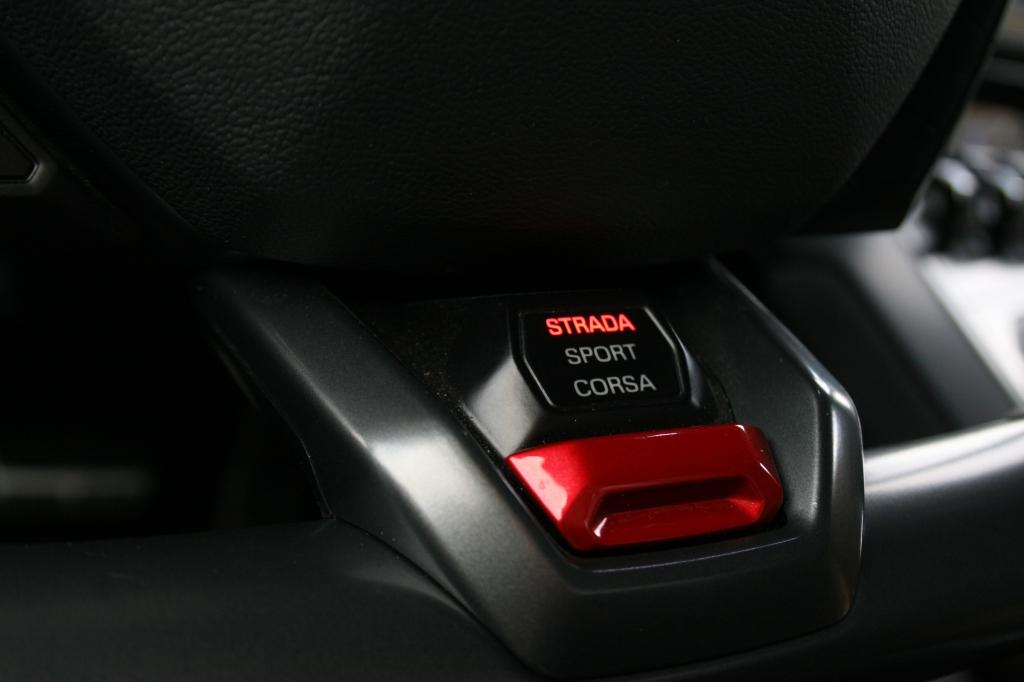 Neders på rattet sidder knappen hvor du vælger mellem Strada, Sport eller Corsa.