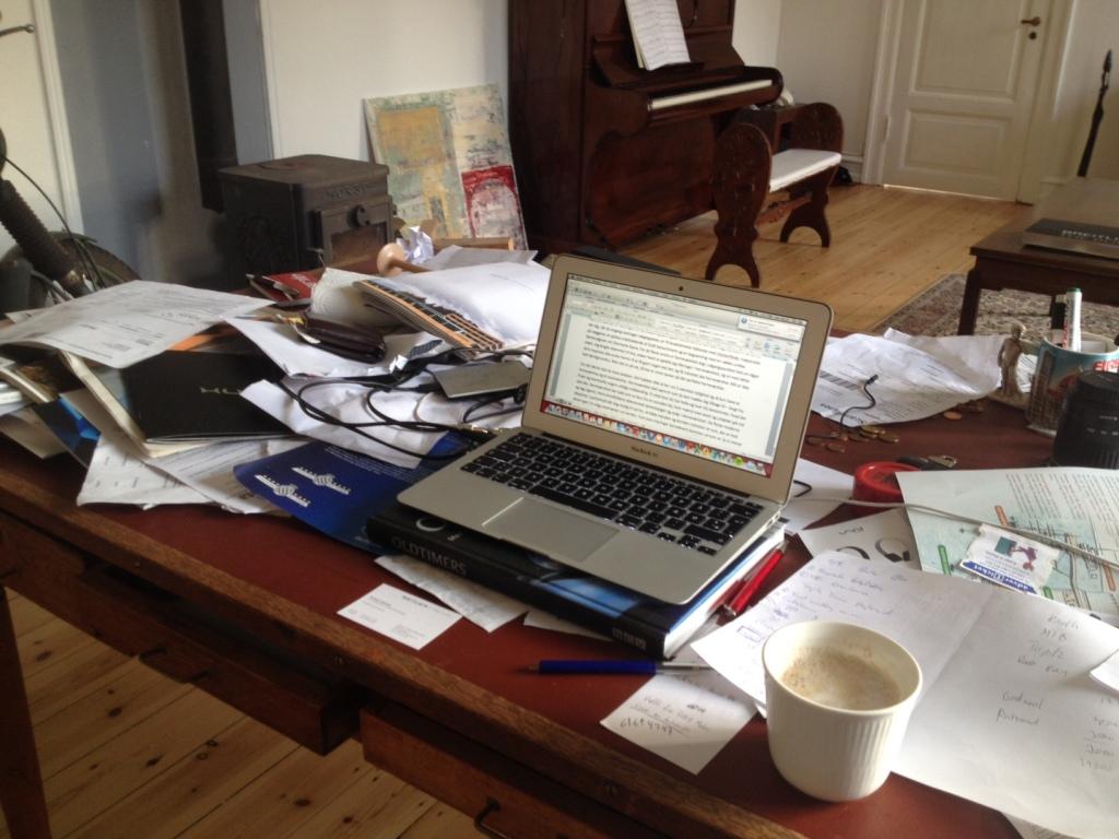 """Rodet? Nej - sådan ser der altid ud, og ingen blander sig. Jeg kalder mit skrivebord for """"kreativitets-fordrende-udsmykket"""" istedet for rodet."""