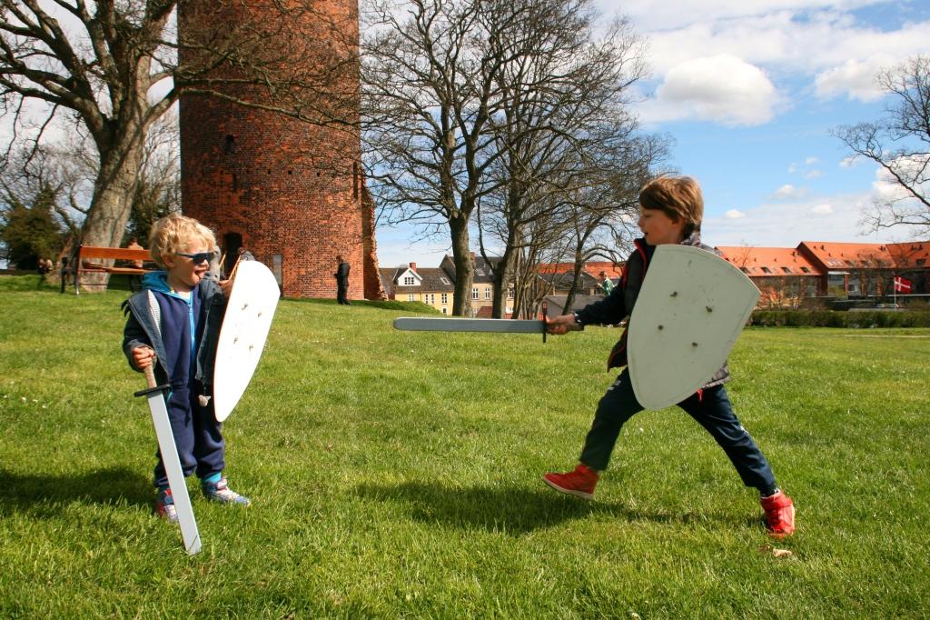 Mine to drenge i drabelig sværdkamp på Vordingborg Borgcenter med Gåsetårnet i baggrunden.
